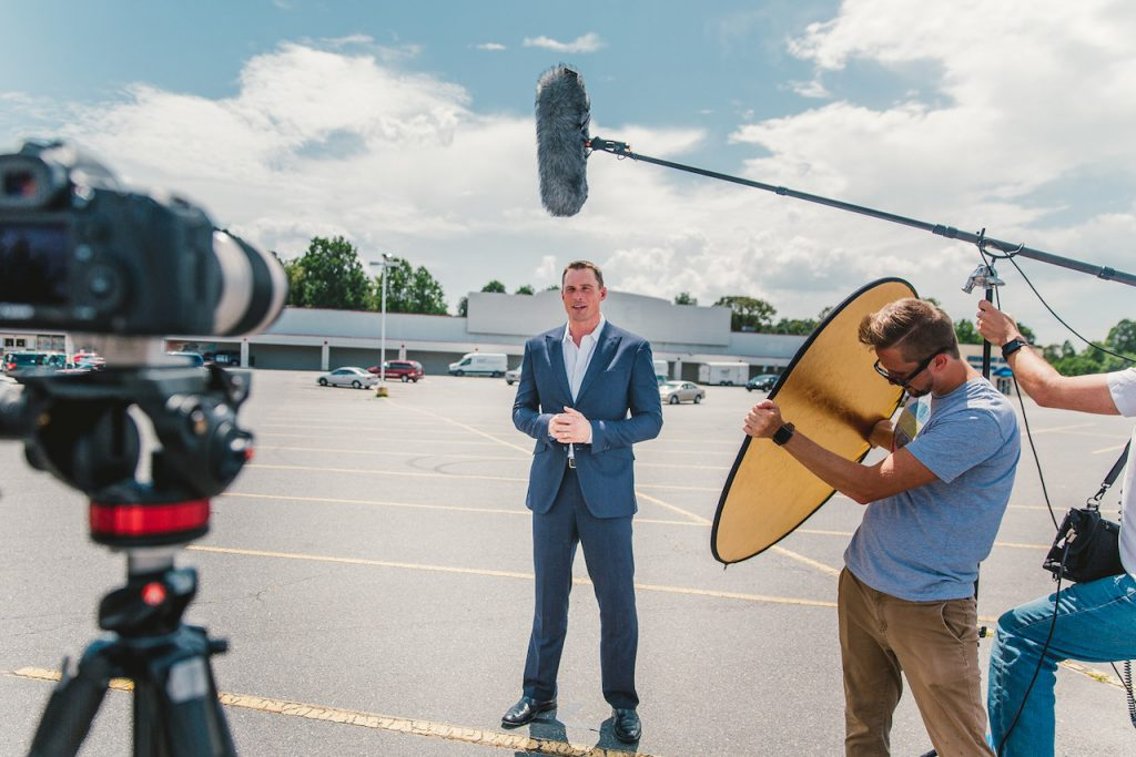 Movement Creative Director Joe Little (at right) jumps in to lend a hand during a video shoot.