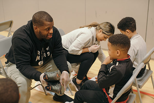 Jonathan Stewart gives shoes to kids.